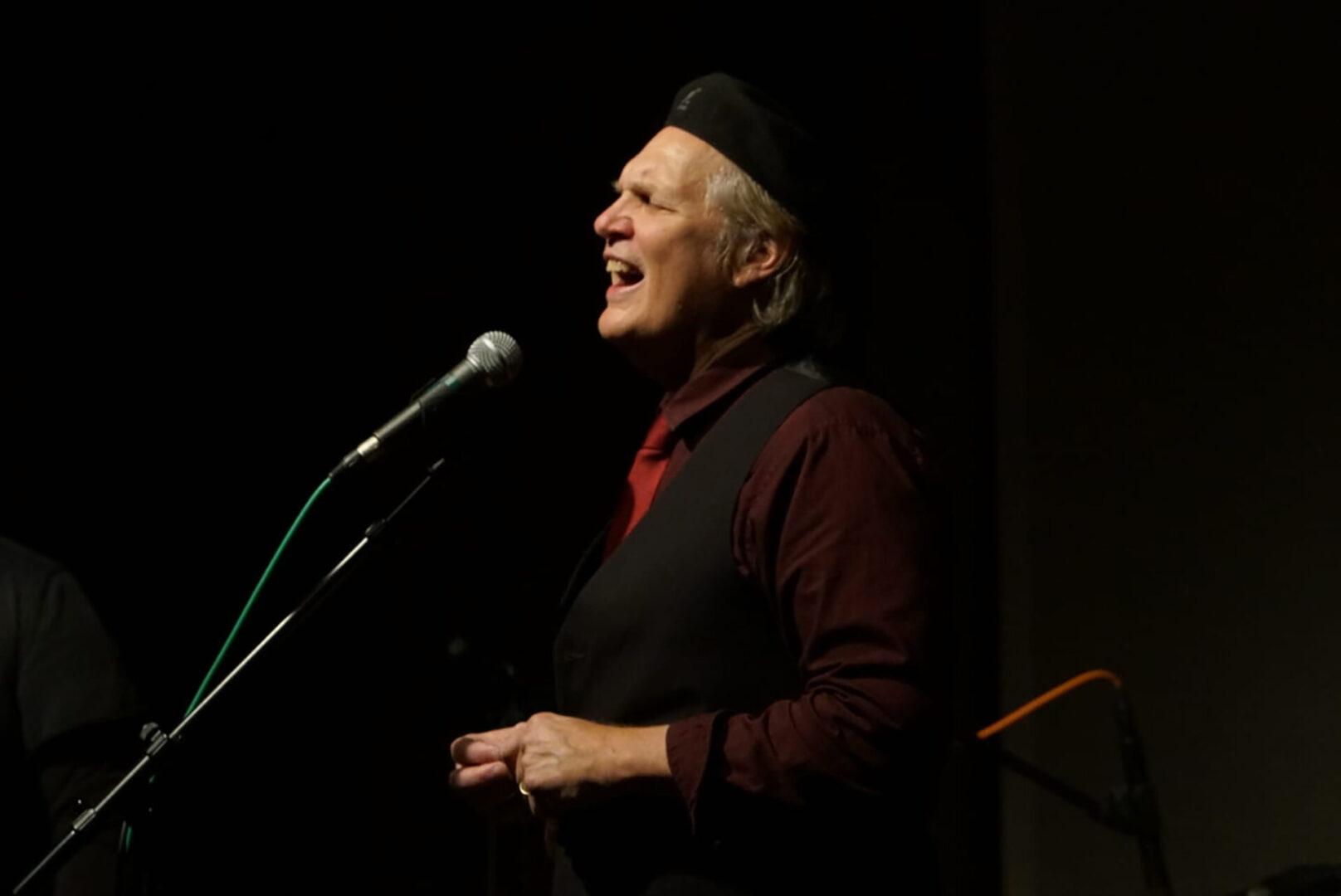 Greg Greenway singing through a microphone