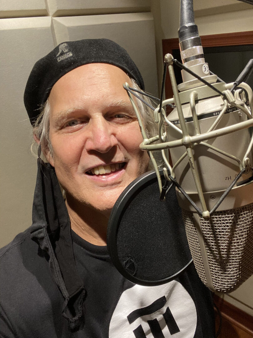 Greg Greenway in front of a mic at a recording booth