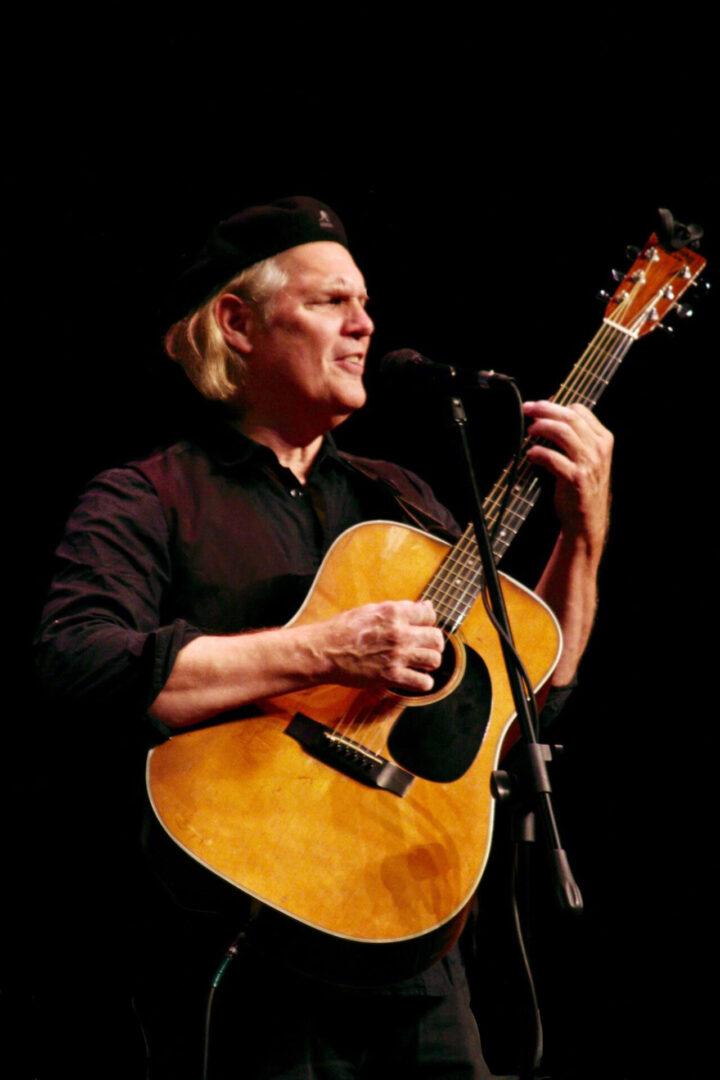 Greg Greenway skillfully playing a guitar